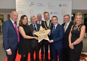 L - R: Peter Sheridan, Chief Executive Co-operation Ireland, Jnr Minister Megan Fearon MLA, Dr Christopher Moran, Chairman of Co-operation Ireland, Tom Dowling, Chairman of the Pride of Place Committee, Lord Mayor of Belfast Brian Kingston, Damien English TD, Minister of State for Housing and Urban Renewal, George Jones IPB Chairman and Suzanne Wylie, Chief Executive Belfast City Council